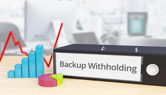 Backup Withholding - Finance/Economy. Folder on desk with label beside diagrams. Business/statistics