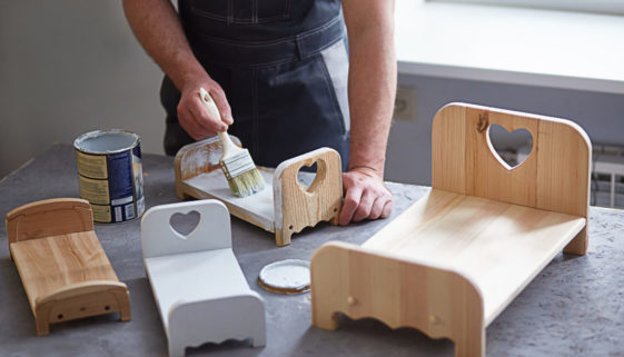 Faceless man at work as a craftsman in a workshop paints wooden doll beds. The workspace of a small business or hobby